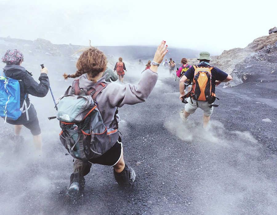 personas descendiendo por las cenizas y la lava